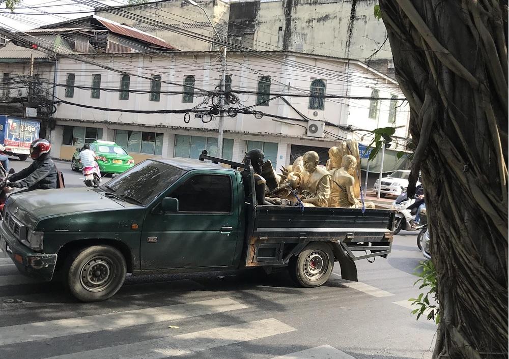 Zielony samochód przewożący złote figury